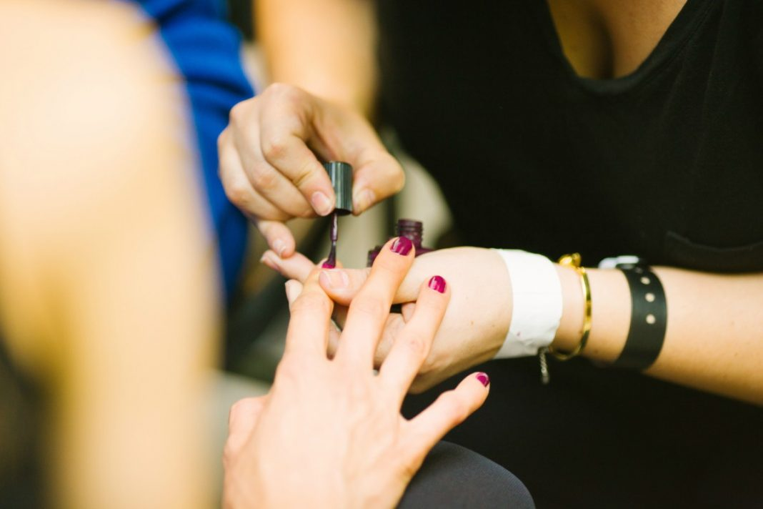 woman gets her nails polished