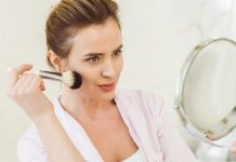 woman-applying-makeup-in-the-mirror
