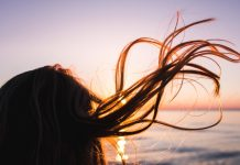 woman stands before sea and her hair is blowned by the wind