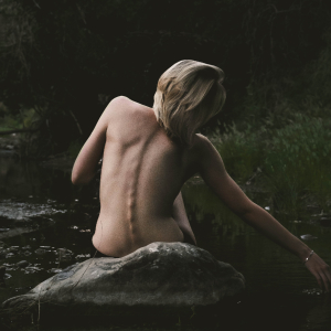 woman sitting on a rock in a lake