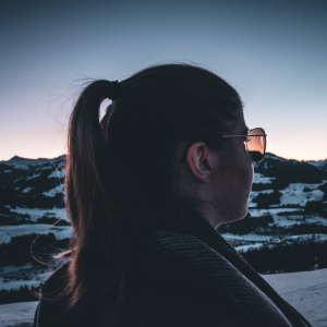 woman with ponytail and glasses looking at the mountains