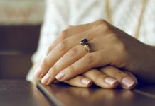 person wearing silver colored ring with black gemstone