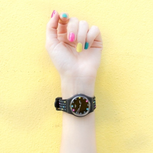 picture of a person with a watch and colorful nails